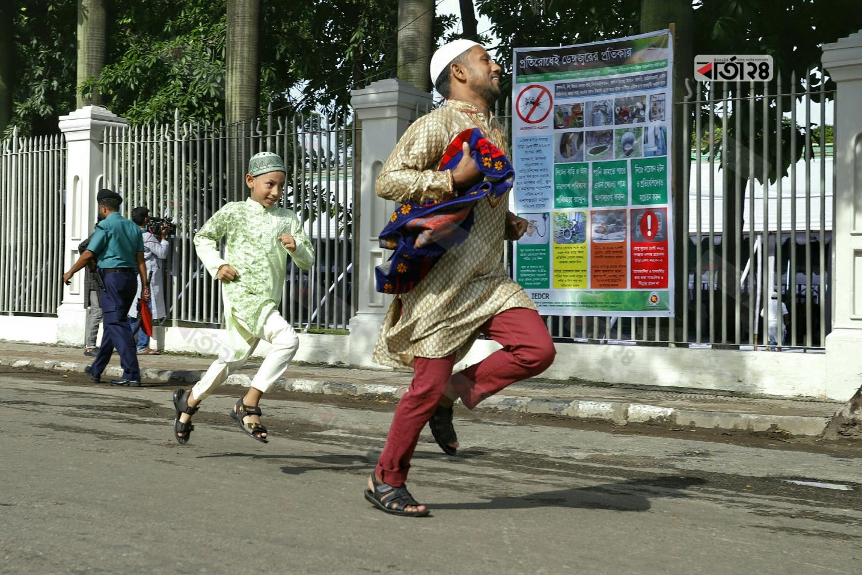 জামাতে দেরি হওয়ায় ঈদগাহ ময়দানের দিকে দৌড়াতে থাকে মুসল্লিরা। ছবি : সুমন শেখ