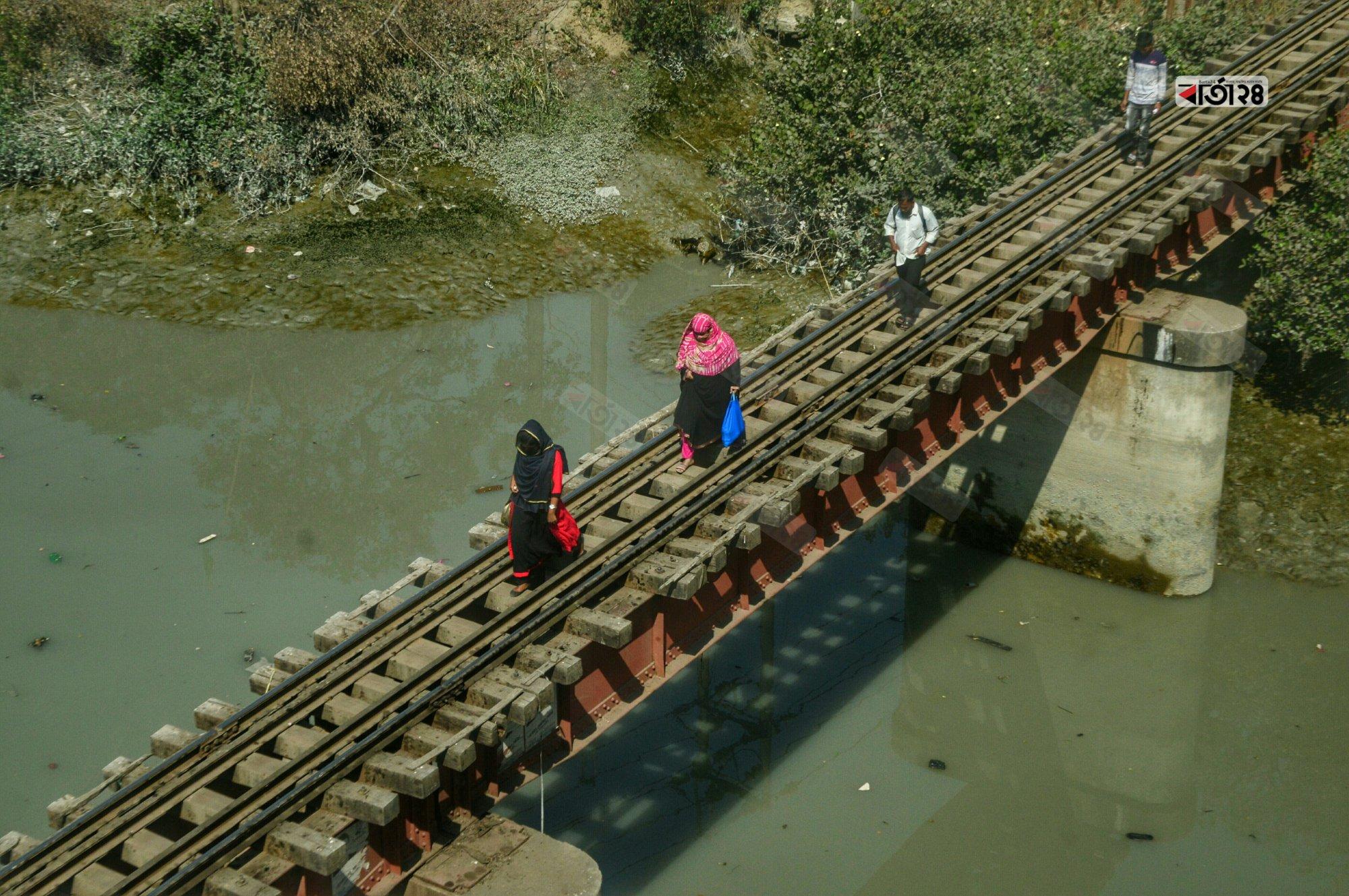 পথচারীরা জীবনের ঝুঁকি নিয়ে পার হচ্ছে চট্টগ্রাম বন্দর এলাকার ক্রসিং মোড়ের রেলসেতুটি। ছবি : সুমন শেখ