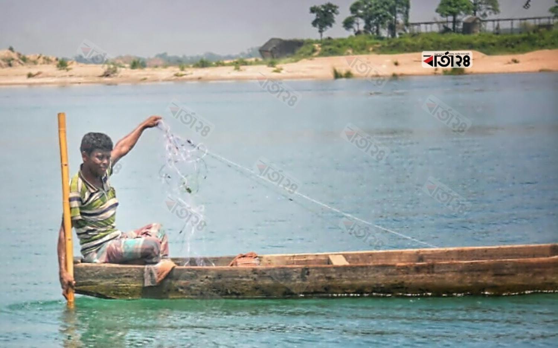 সিলেটের ধলাই নদীতে কারেন্ট জাঁল দিয়ে মাছ ধরছেন এক জেলে। ছবি: আবু বকর।
