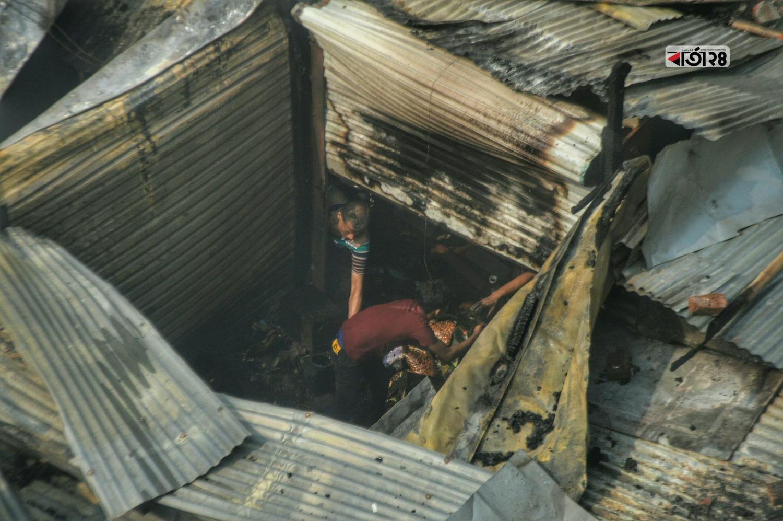 পুড়ে যাওয়া দোকানে মূল্যবান জিনিসের খোঁজে এক দোকানি। ছবি: সুমন শেখ